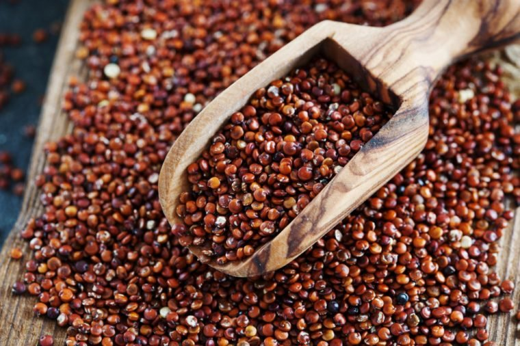 Seeds of red quinoa in wooden scoop. Chenopodium quinoa background close up, copy space