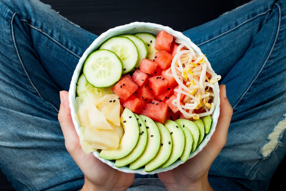 Girl in jeans holding hawaiian watermelon poke bowl with avocado, cucumber, mung bean sprouts and pickled ginger. Top view, overhead