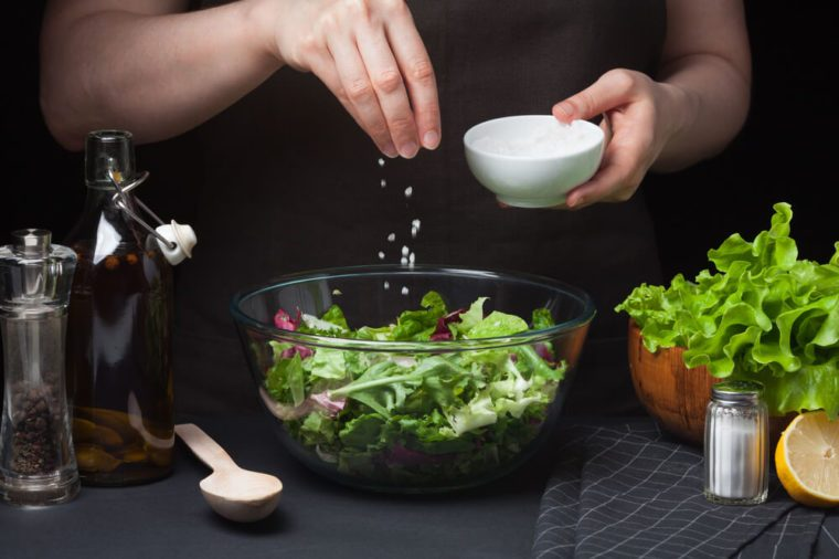 Woman chef in the kitchen preparing vegetable salad. Healthy Eating. Diet Concept. A Healthy Way Of Life. To Cook At Home. For Cooking. The girl sprinkles sea salt in a salad on a dark background