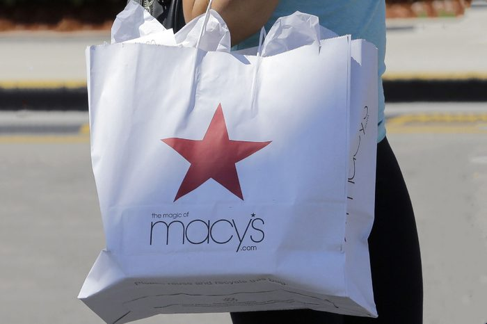 A shopper carries a bag as she walks in the parking lot of a shopping mall in Hialeah, Fla. Macy's Inc. reports earnings, Thursday, Aug. 10, 2017