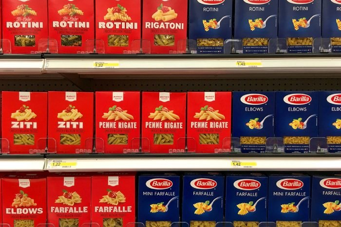 Alameda, CA - July 21, 2017: Grocery store shelf with boxes of generic brand Market Pantry pasta next to name brand Barilla pasta.
