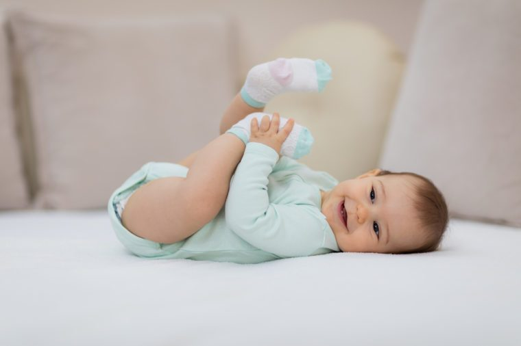 Happy baby lying on white sheet and holding her legs / Playful baby lying down in bed
