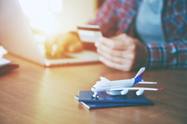 Airplane with passports near paying with credit card and laptop. Online ticket booking concept