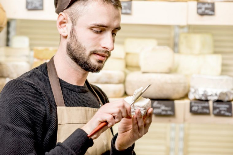 Portrait of a handsome seller in uniform cutting young cheese in front of the store showcase full of different cheeses