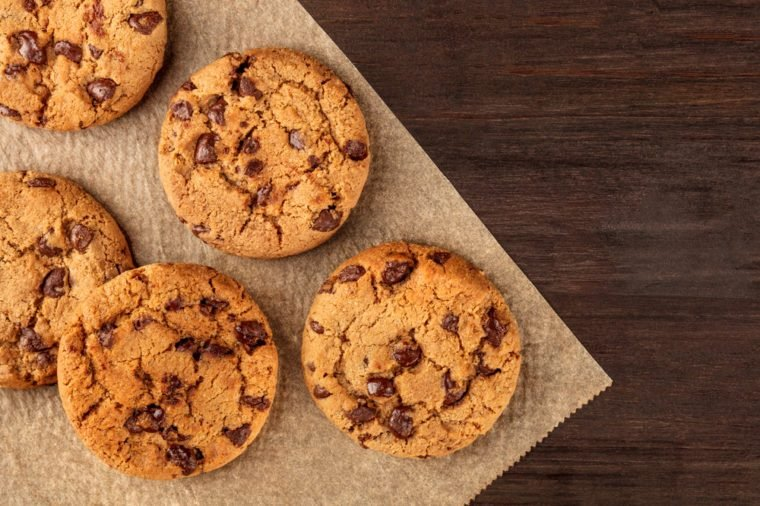 An overhead photo of chocolate chips cookies, shot from above on a piece of baking paper, with copy space