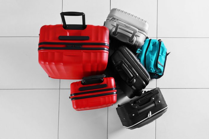 Different suitcases on tile floor, top view