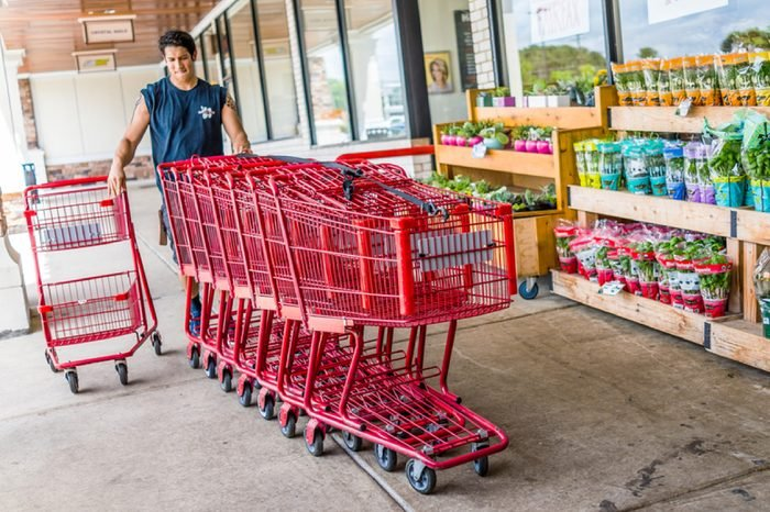 Fairfax, USA - January 18, 2017: Happy Trader Joe's employee returning shopping carts to the store outside entrance with woman customer