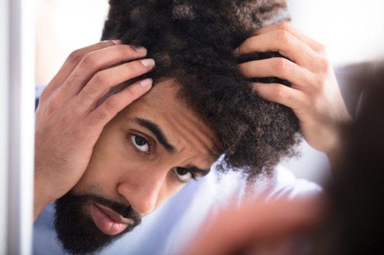 Close-up Of A Young Man Examining His Hair