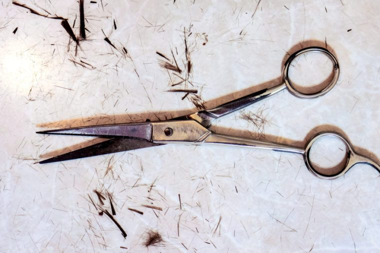 single open silver hair cutting shears against small spots of dark cutting hair and many small filaments on the table after haircut. Work still life of hairdresser