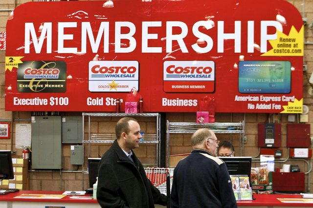 In a photo made, Consumers apply for Costco membership at the Costco Wholesale store in Glendale, Calif. Costco's fiscal third-quarter net income climbed 19 percent on lower asset charges and the wholesale club pulled in more money from membership fees