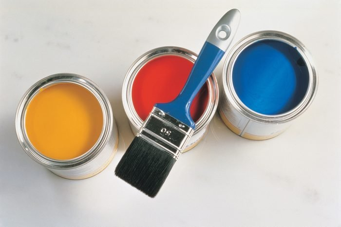 Interior and Decoration - a group of colorful paint cans with paintbrush isolated on silver background