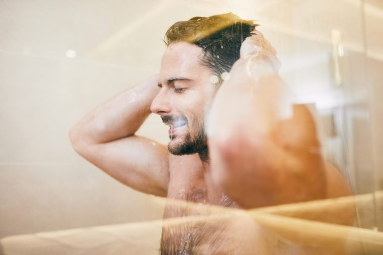 relaxed man taking shower with closed eyes