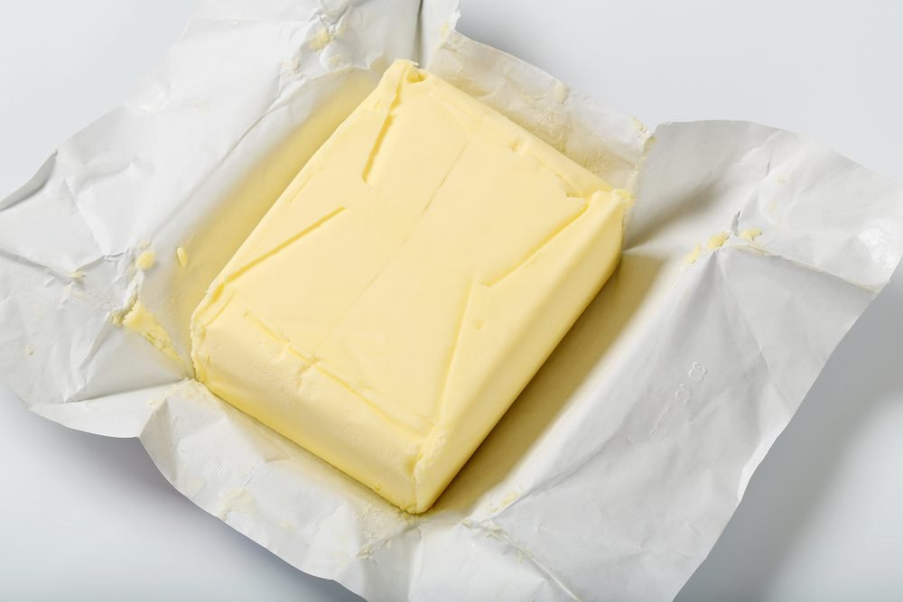 block of fresh butter on white background - close up