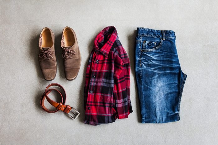 Men's casual outfits with red plaid shirt, blue jeans, casual shoes and belt on gray background, fashion and beauty concept, flat lay