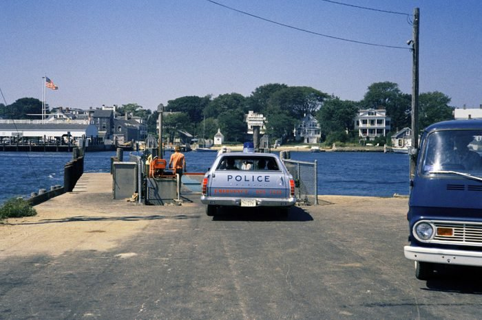 Police car waits to board and cross on ferry from Chappaquiddick Island to Edgartown, Mass. on