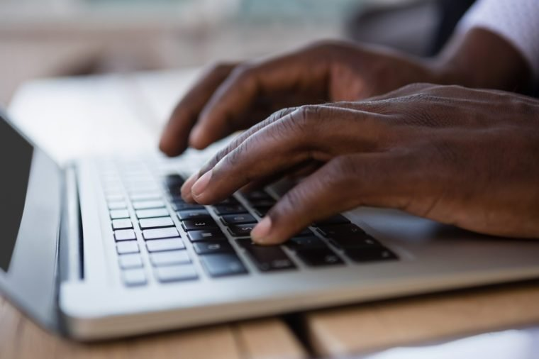 Cropped hands of businessman using laptop on table