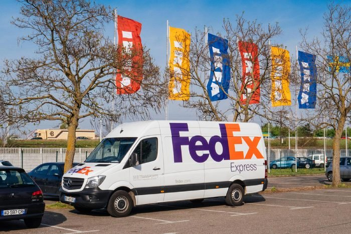 PARIS, FRANCE - APR 10, 2017: White FEDEX parcel delivery van parked in front of the IKEA furniture store with multicolor IKEA flags waving in the background
