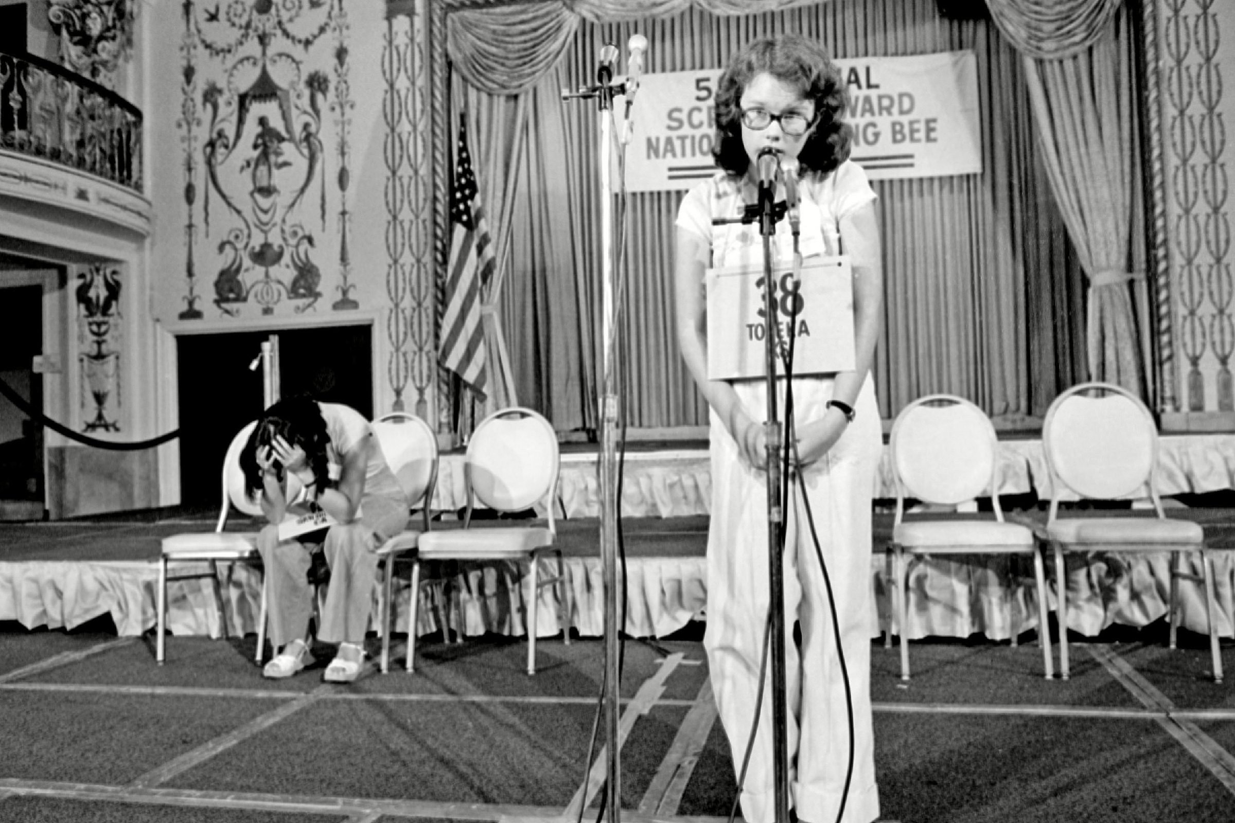 """Peg McCarthy, Lyn Sue Kahng Peg McCarthy of Topeka, Kansas, spells the world """"deification"""" to win the 51st National Spelling Bee in Washington, D.C., . The runner-up Lyn Sue Kahng, seated left, puts her head in her hands. Kahng is from San Diego"""