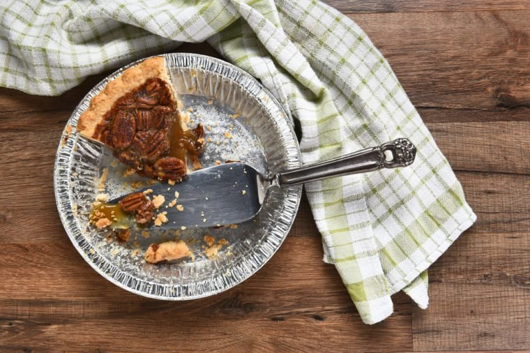 The last slice of a Thanksgiving holiday pecan pie. A tin with spatula on a wood table with kitchen towel.