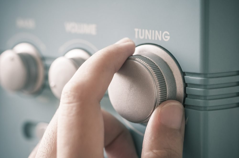 Hand tuning fm radio button. Retro image processed.