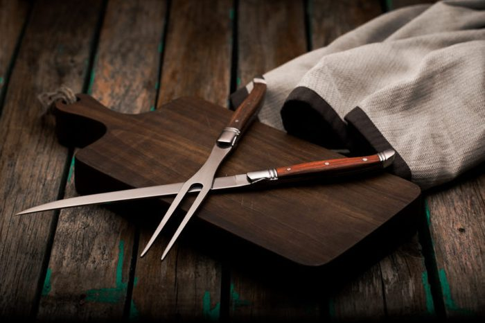 Fork and sharp knife for meat on the board