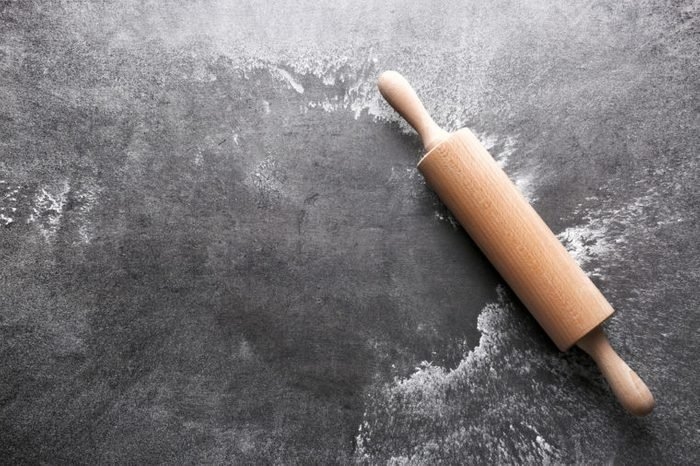 Scattered flour and rolling pin on gray background