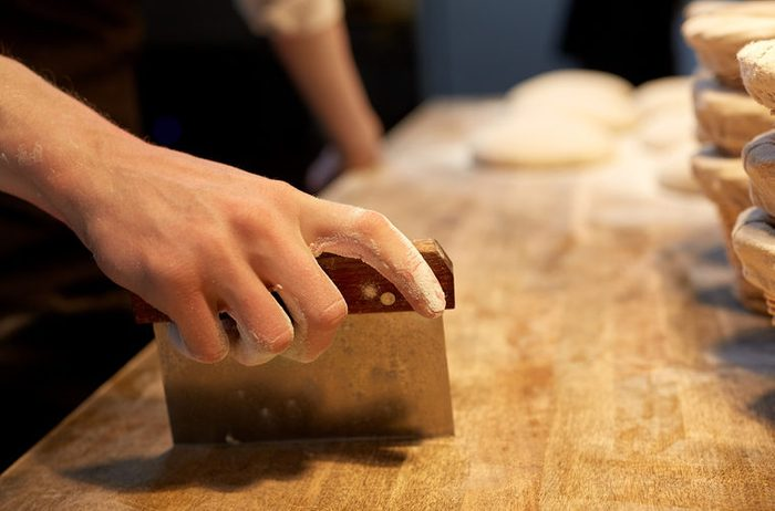 food cooking, baking and people concept - chef or baker portioning dough with bench cutter at bakery