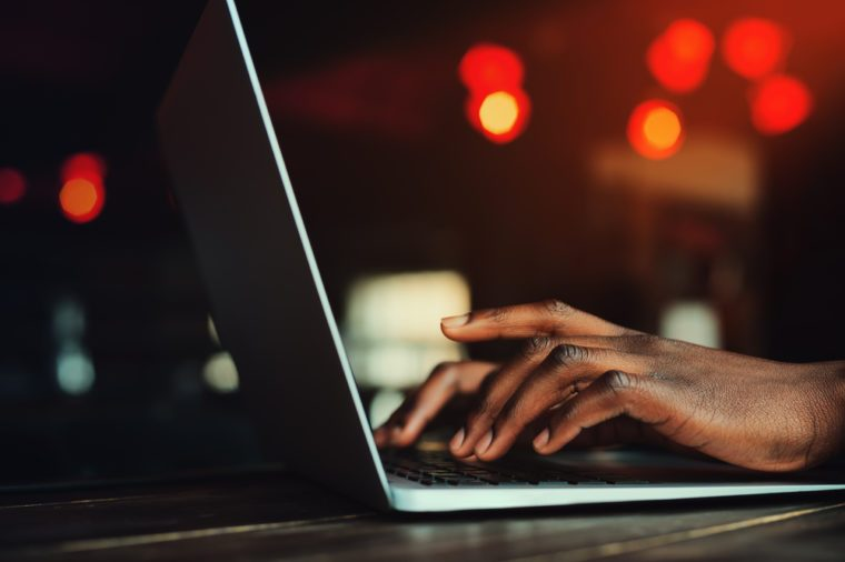 Black man's hands typing on laptop keyboard. Person working with laptop. Beautiful lights as background. Toned style instagram filters. Selective focus