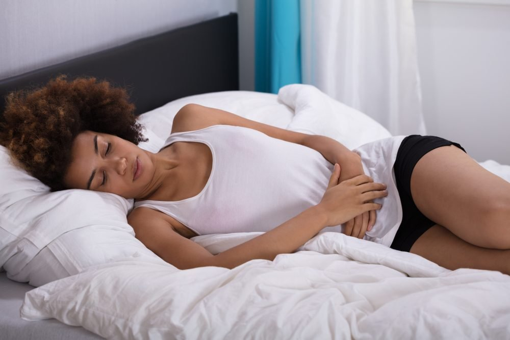 woman with stomach pain lying in bed
