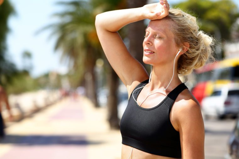 Runner girl tired feeling exhausted from jogging outside in summer heat -sun stroke headache or dehydration during difficult training outdoors. Blonde fitness woman model touching forehead.