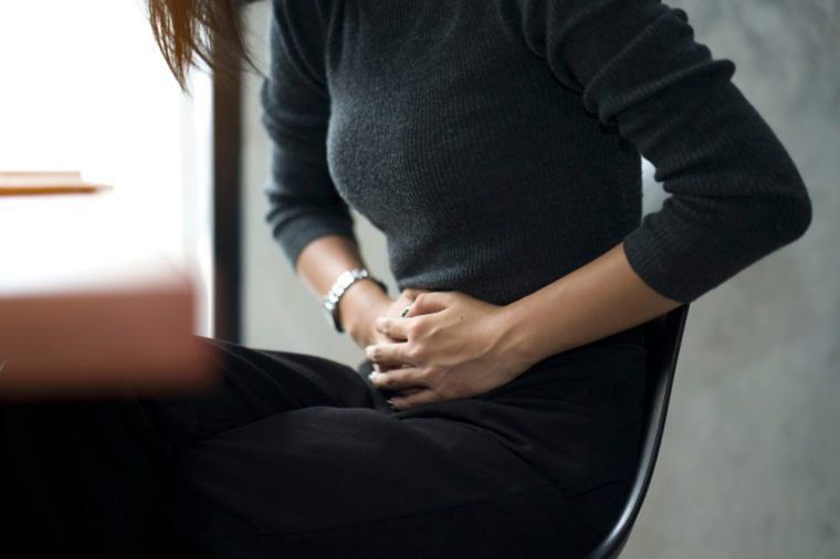 Business woman feeling painful from stomachache illness during working at office, hands touching her stomach and awareness of her Appendicitis sickness. Health insurance care. Insurance concept.
