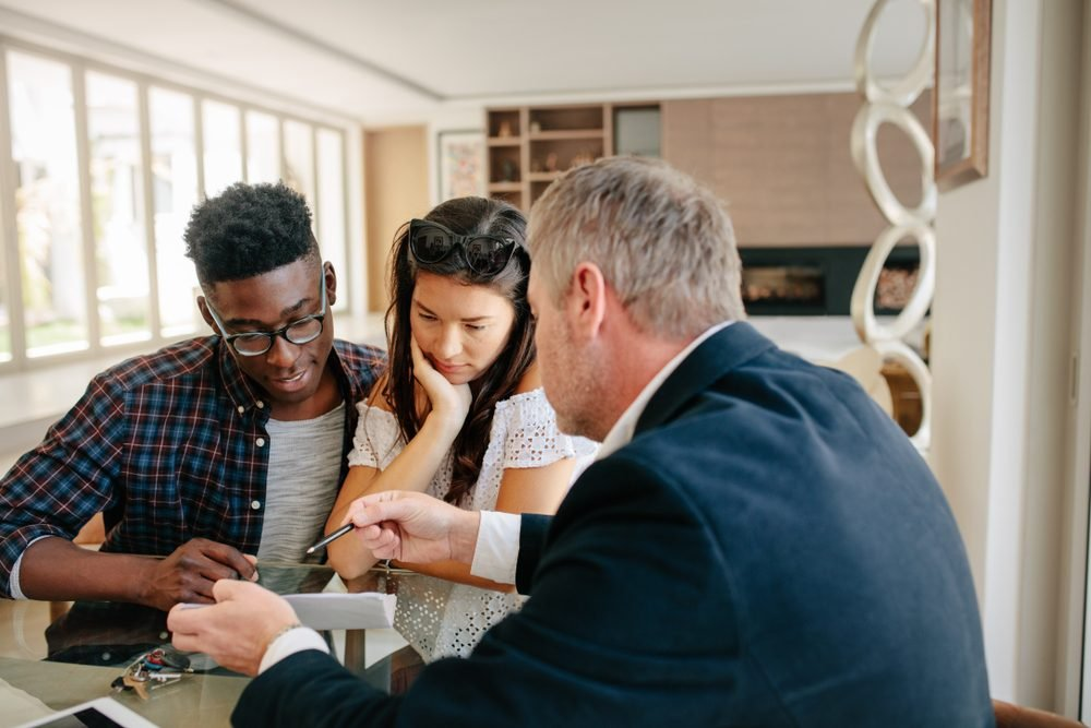 Financial consultant explaining every detail of mortgage to couple. Realtor explaining lease agreement or purchase contract to couple in an apartment.