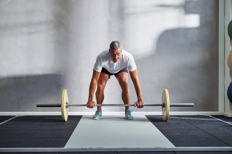 Focused senior man in sportswear standing alone in a gym lifting weights during a workout