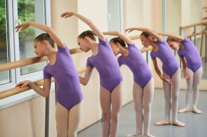 Group of ballerinas training at ballet barre. Young ballet girs in purple leotards practicing at ballet class. Tips for beginning ballet.