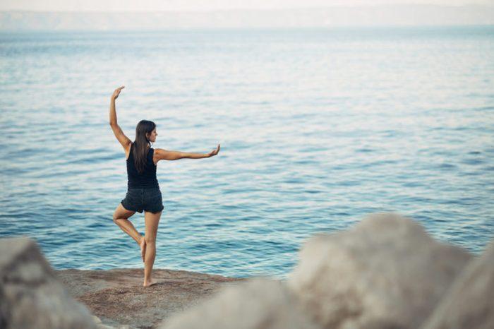 Carefree woman meditating in nature.Finding inner peace.Yoga practice.Spiritual healing lifestyle.Enjoying peace,anti-stress therapy,mindfulness meditation.Positive energy.Tree pose,Vrksasana