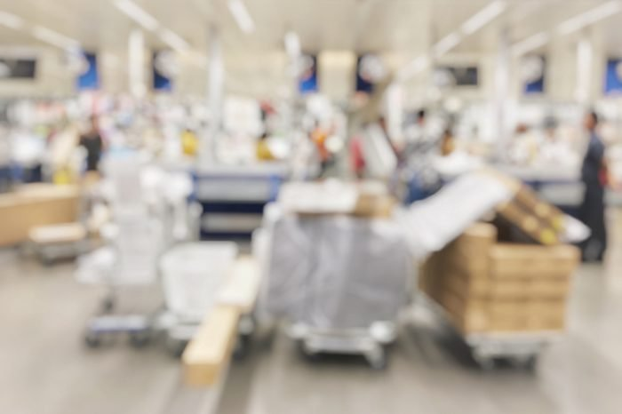Blurred image of businesswoman is going to finding furniture for her business home with shopping mall cart in house and hardware department store background, store shopping mall background.