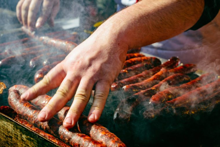 Man grills sausages. Grilled sausage on barbecue, grill. Shallow depth of field.