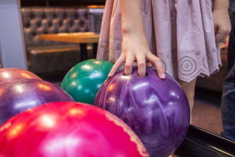 Girl holding bowl colorful variety game indoor.