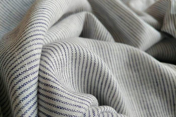 Lightweight linen scarf. Natural organic flax, linen cotton blend fabric background.