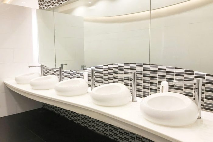 Row of modern white ceramic wash basin in public toilet or restaurant or hotel or shopping mall, interior design