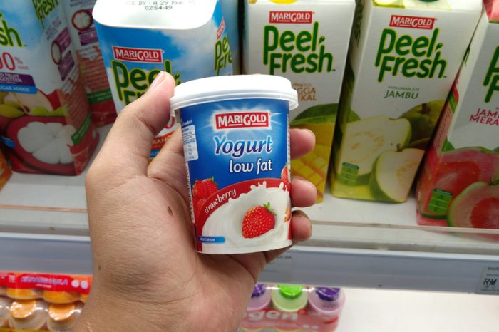 KLANG, MALAYSIA - MARCH 17, 2018 : Hand holding a cup of Marigold Low Fat Yogurt in hypermarket.