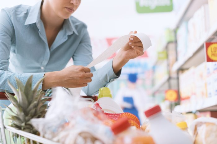 Woman shopping at the supermarket, she is checking a long grocery receipt and leaning on a cart, budgeting and lifestyle concept