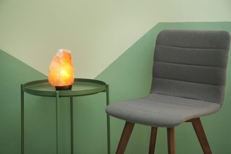 Himalayan salt lamp on table near color wall