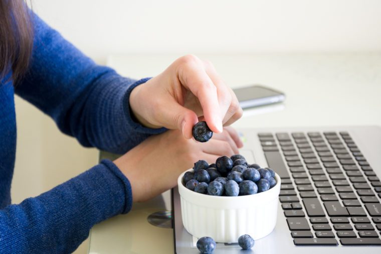 Young woman using laptop computer at home and eating blueberry.