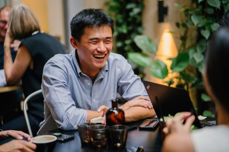 A group of young and energetic Chinese Asian coworkers sit around a table and have a light hearted business discussion. They are smiling and laughing as they talk and have a conversation.