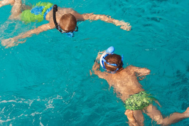 Two children swim in the ocean with snorkeling mask. Summer background