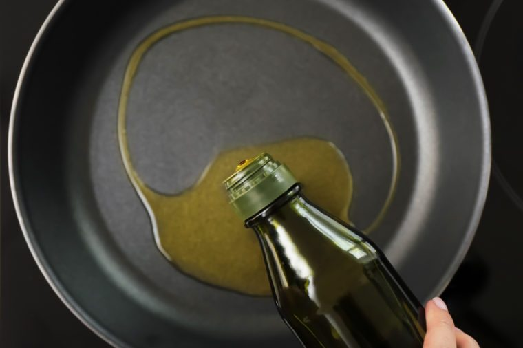Woman pouring olive oil onto frying pan on stove