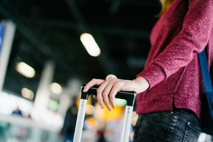 Close up photo of female passenger standing near the window checking time on smart watch while waiting for delayed flight in the international airport terminal. Cropped shot with blurred background.