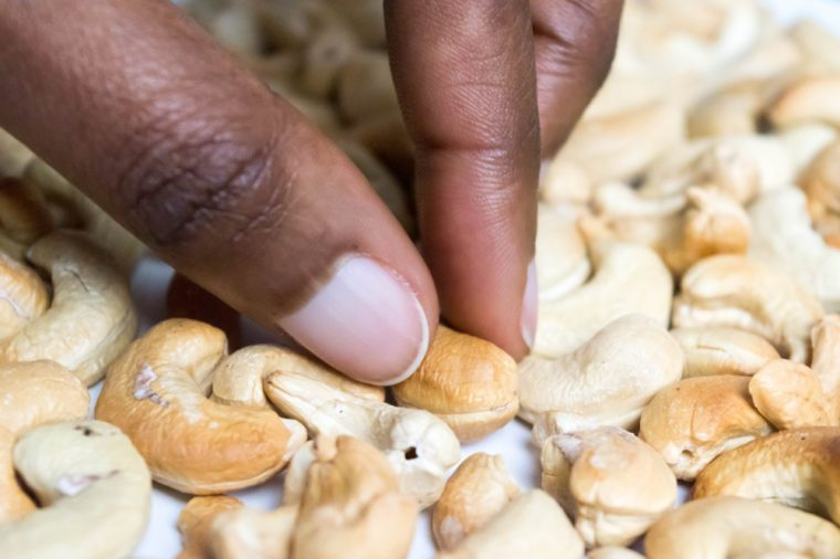 Picking Cashews with African American Dark Brown Skin hand on white background