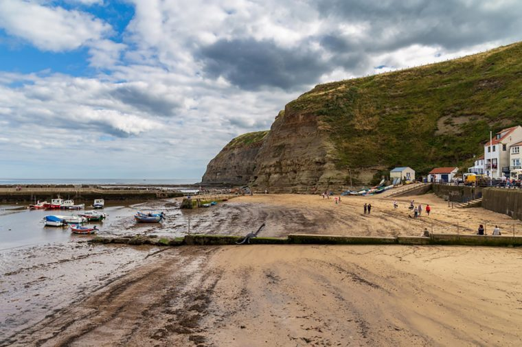Staithes, North Yorkshire, England, UK - September 07, 2016: View across the beach with some boats and people
